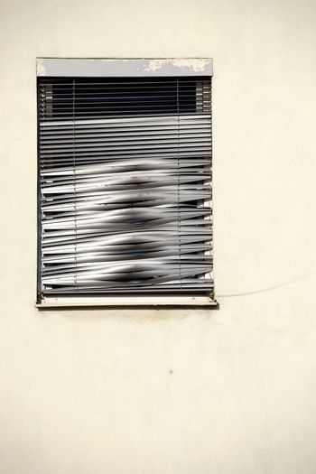 The closeup of a single window with a shiny metallic broken blind.