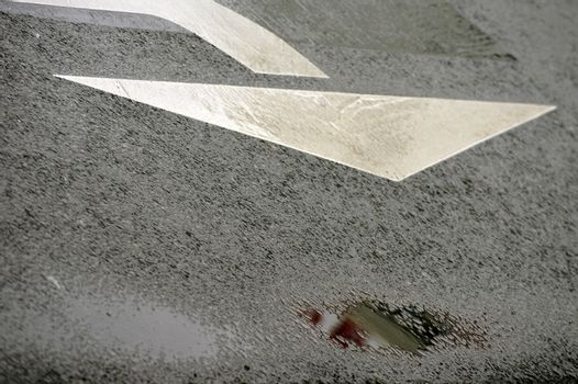 In a rain puddle on the tar paving of a street are reflected abstract colors.