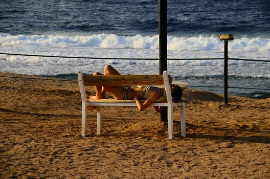 young woman in bikini lying on a bench on the sandy beach and sea