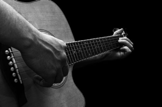 The photo depicts a young man playing a guitar
