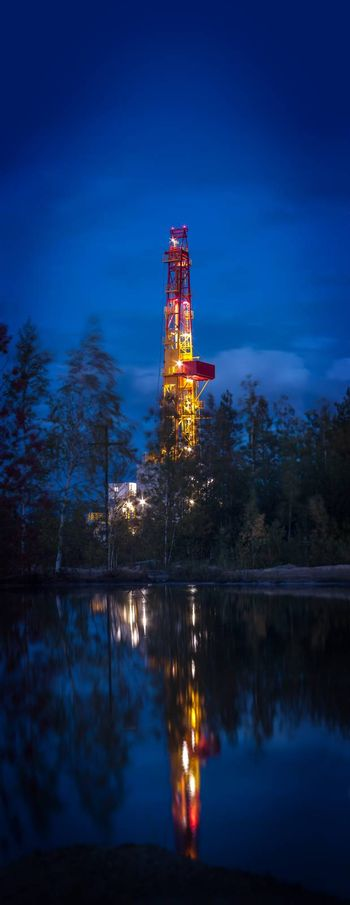 Night landscape with the drilling rig. Vertical panorama. Selective focus, shallow depth of field.