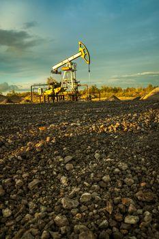 Oil pump jacks at sunset sky background.