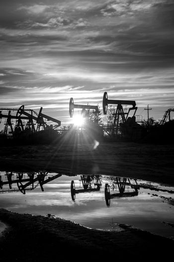 Oil pump jacks at sunset sky background. Black and white.