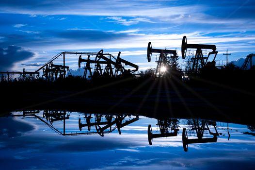 Oil pump jacks group on a sunset sky background. Toned blue.
