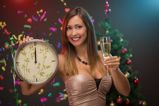 Happiness beautiful woman celebrating New Year. She is showing midnight on the clock and toasting with champagne. Confetti is the air.