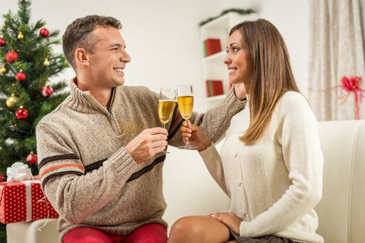 Romantic young couple at home toasting Christmas with champagne.