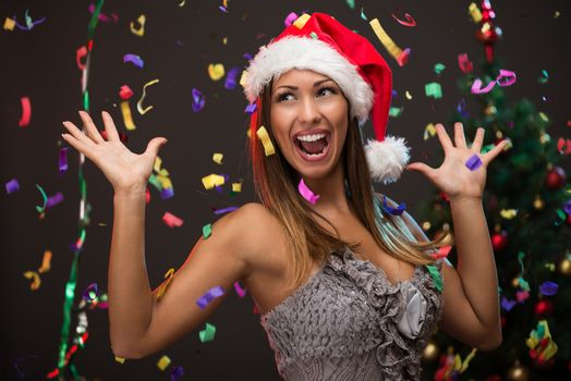 Cheerful beautiful woman celebrating New Year. She is having fun, confetti is in the air.
