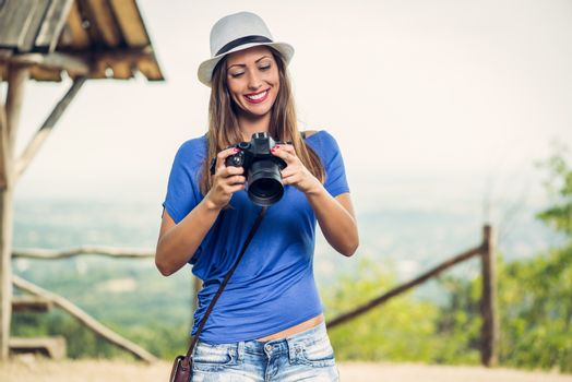 Young beautiful woman standing by viewpoint and looking photography on the digital camera.