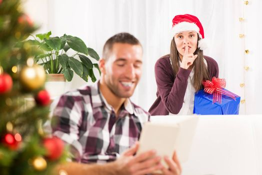 Young beautiful girl has a Christmas present for her boyfriend and she wants to surprise him.