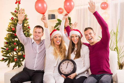 Happy friends Celebrating New Year in home interior with arms raised and showing midnight on the clock.