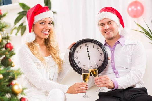 Happy beautiful couple Celebrating New Year in home interior and showing midnight on the clock.