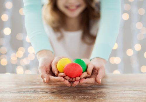 easter, family, people, holiday and childhood concept - close up of happy girl and mother hands holding colored eggs over lights background