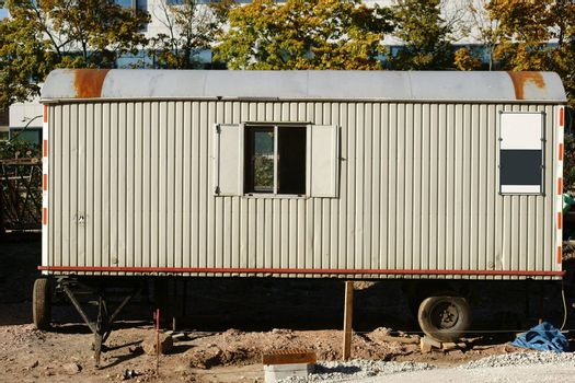 The side view of an old construction trailer on a construction site.