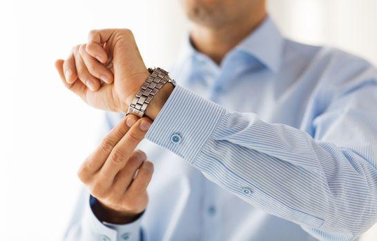 close up of man in shirt fastening wristwatch
