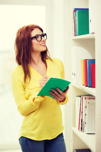 female student in eyeglasses with textbook