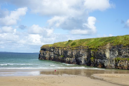 lone kayaker and tourist near the cliffs of ballybunion beach on the wild atlantic way ireland