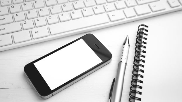 computer and cellphone with notebook and pen black and white col