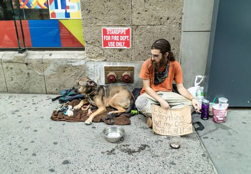 NEW YORK, USA, October 10, 2015: An unidentified homeless with his dog in Manhattan, New York City.