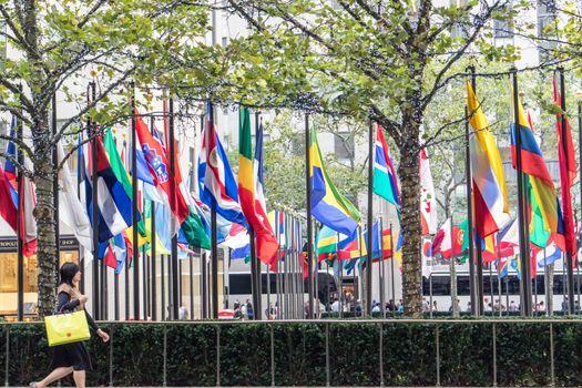 NEW YORK, USA, October 10, 2015: An unidentified woman walks in front of Rockfeller Center flags in Manhattan, New York.