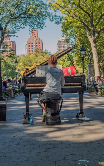 NEW YORK, USA, October 10, 2015: An unidentified lonely girl plays her piano in Washington Square Garden in Manhattan, New York.