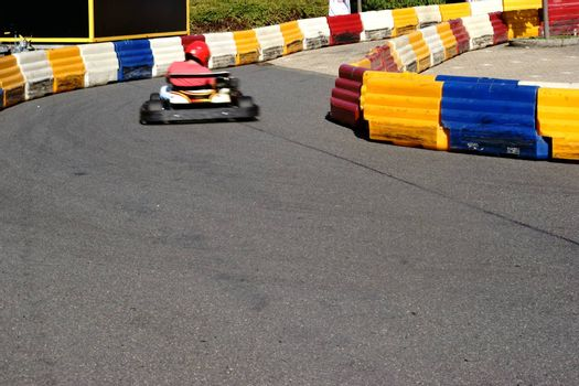 A racer in a kart driving on a limited kart track through the curve.