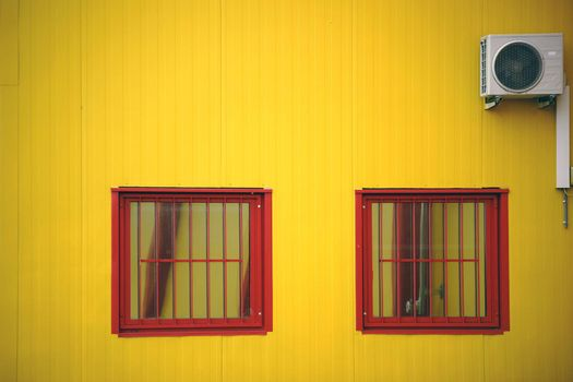 The yellow side wall of a shopping mall with two barred windows and a fan.