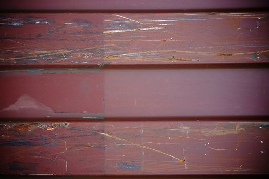 The scratched surface of a metal crate with sanding marks.