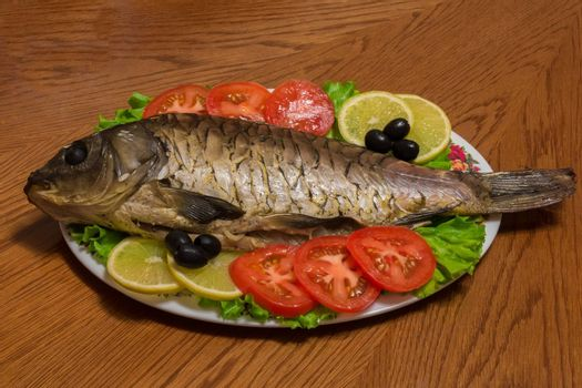 The photo shows a fish on a plate with tomatoes and olives