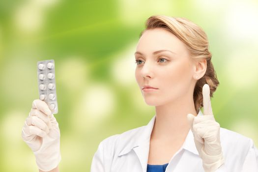 young female doctor with pills pointing finger up