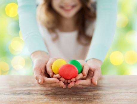 easter, family, people, holiday and childhood concept - close up of happy girl and mother hands holding colored eggs over green lights background