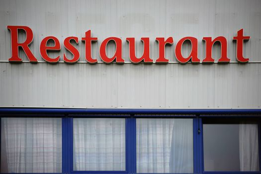 Red big letters of the word restaurant on the facade of a business building.
