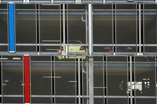 An open parking garage with several parking decks protected by mesh wire.