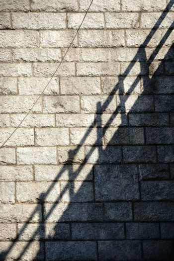 A railing casts a shadow on the stones a rustic wall.