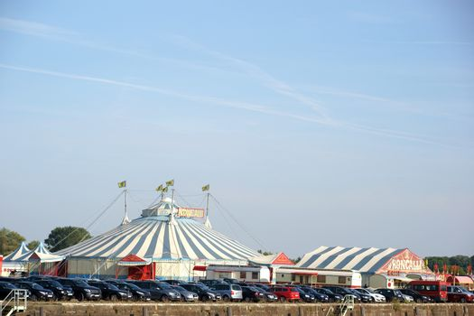 Mainz, Germany - October 02, 2015: The striped circus tent of the Circus Roncalli in the grounds of the harbor Mainz with parked cars on October 02, 2015 in Mainz.