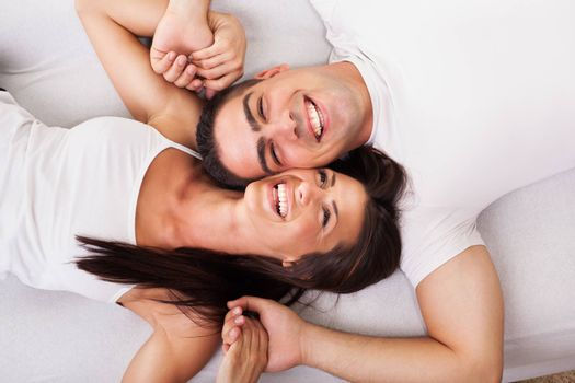 Romantic young couple Lying Down in bed. View from above.