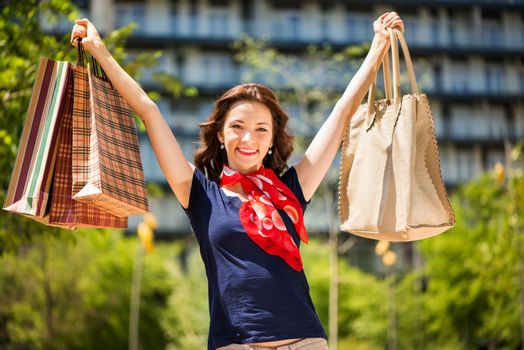 Portrait of beautiful smiling girl standing in front of building with shopping bags. Looking at camera.
