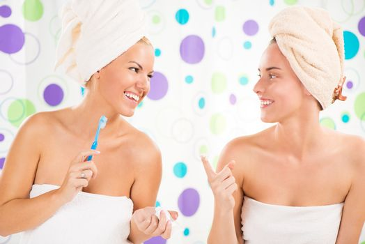 Two young cute woman preparing to start their day. One girl brushing teeth, the other girl applying cream on the face with finger.