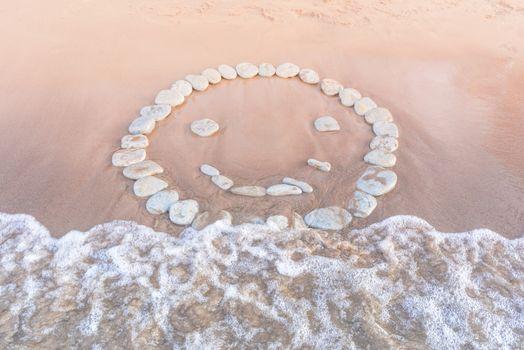 Emoticon of pebbles on sand