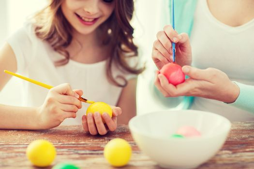 easter, family, holiday and child concept - close up of little girl and mother coloring eggs for easter