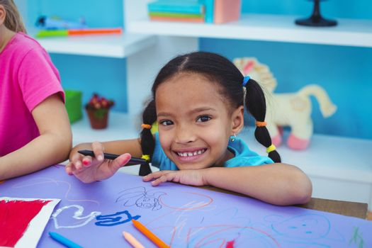 Children drawing on coloured paper