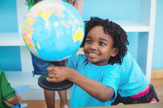 Small boy holding a globe of the world