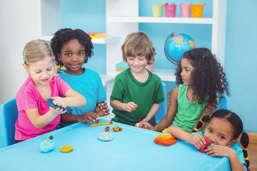 Smiling kids playing with modelling clay