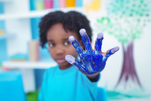 Happy kid enjoying painting with his hands