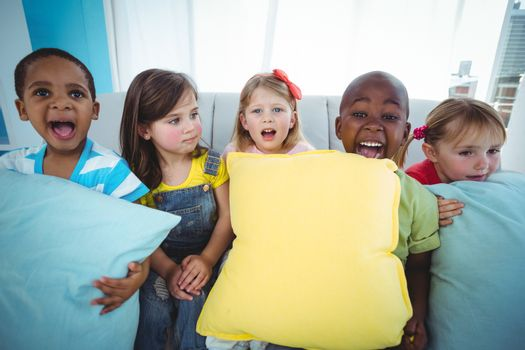 Happy kids holding couch cushions
