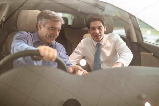 Businessman pointing a car interior