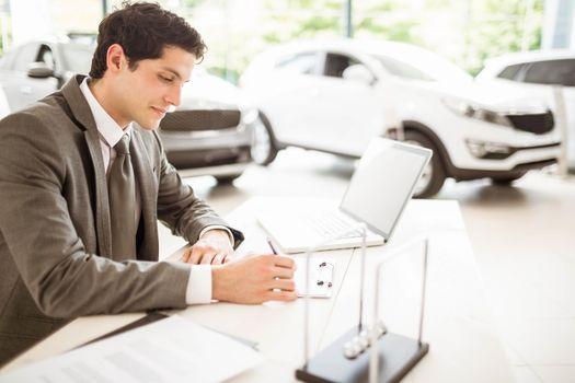 Smiling salesman at his desk