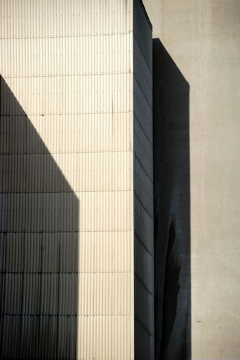 The corners and edges of an industrial building cast geometric shadows.