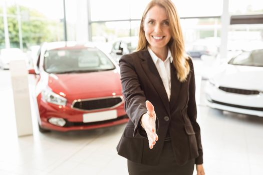 Smiling businesswoman reaching her hand