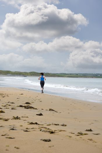 young woman jogging on the beach in ballybunion county kerry ireland