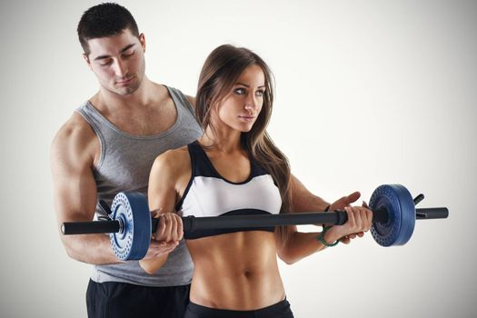 Young beautiful woman practicing Biceps muscle group with personal trainer.